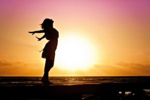 silhouette of a woman throwing her hands back in front of a sunset