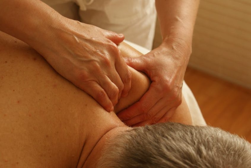 man getting shoulder massage physiotherapy